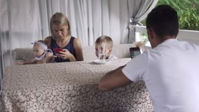 Little boy has fun with parents using phones in cafe stock video footage