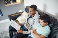 Giving Dad a Homemade Father`s Day Card. Little boy has given his father a homemade card for Father`s Day. They are relaxing on the sofa looking at it together royalty free stock image