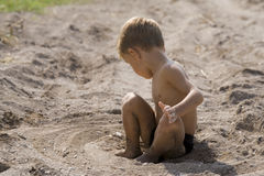 Little boy has outlined round itself a circle. The little boy sitting on sand, has outlined round itself a circle Royalty Free Stock Photos