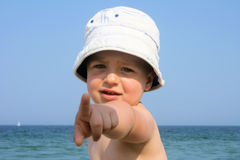 Little boy in hat at the beach pointing to camera Stock Images