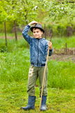 Little boy in hat and boots outdoor. Full length portrait of a boy with hat and boots, holding a cane outdoor Stock Photos