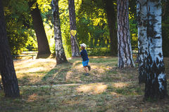 Little boy with hat and butterfly net run in wood or park Royalty Free Stock Photos