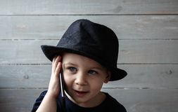 A little boy in a hat holds a phone stock photos