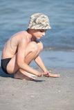 Little boy with hat playing on the beach Royalty Free Stock Images