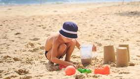 Little Boy in Hat Squats Digs Hole Fills Bucket with Sand. Little boy in panama squats digs hole fills bucket with sand on golden sand beach near wave surf and stock video