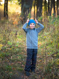 Little boy in hat standing in the grass and shows horns Stock Photo