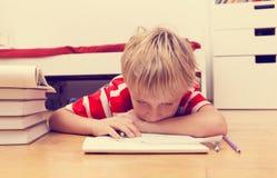 Little boy hates doing homework Stock Photo