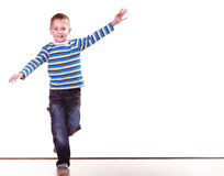 Little boy have fun alone at home stand on one leg. stock images