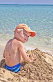 Little boy have fun digging in the sand Stock Images