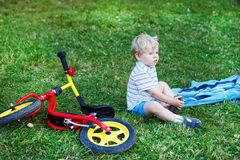 Little boy having break on green grass after riding bicycle. Royalty Free Stock Photography
