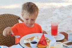 Little boy having breakfast at the resort Stock Image