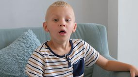 Little boy having a cough, sitting on a sofa in living room stock video