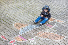 Little boy having fun with airplane picture drawing with chalk Royalty Free Stock Photography