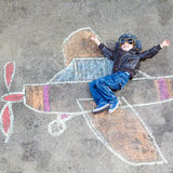 Little boy having fun with airplane picture drawing with chalk Stock Photo