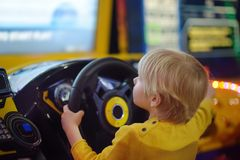 Little boy having fun in amusement in play center. Kid playing racing simulator game in Arcade centre stock image
