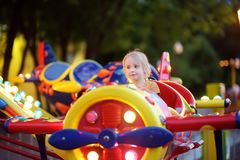 Little boy having fun on attraction in public park. Child riding on a merry go round at summer evening. Attraction, planes, cars, royalty free stock images