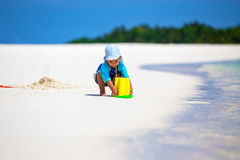 Little boy having fun on the beach while building a sand castle Stock Photography