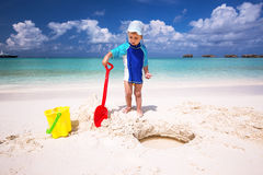 Little boy having fun on the beach while building a sand castle. On tropical Maldives island Stock Photography