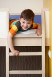 Little boy having fun on bunk bed laughing Stock Photos