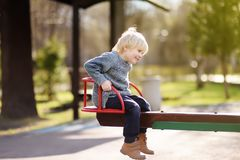 Little boy having fun with carousel on outdoor playground Royalty Free Stock Image