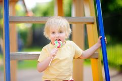 Little boy having fun and eating big lollipop on outdoor playground Royalty Free Stock Photos