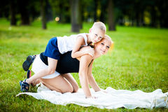 Little boy having fun with his mother. In a park during beautiful summer evening Stock Image