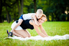 Little boy having fun with his mother. In a park during beautiful summer evening Stock Photo