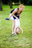 Little boy having fun with his mother. In a park during beautiful summer evening Stock Photos