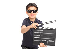 Little boy having fun with a movie clapperboard. Little boy with sunglasses and a black beret having fun with a movie clapperboard isolated on white background Royalty Free Stock Image
