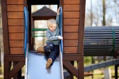 Little boy having fun on outdoor playground/on slide Stock Photos
