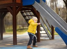 Little boy having fun on outdoor playground on spring or fall day Royalty Free Stock Photo