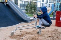 A little boy is having fun playing on the modern urban European playground.  stock photo