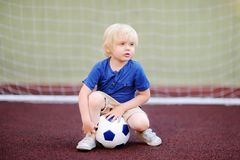 Little boy having fun playing a soccer/football game on summer day Stock Photography
