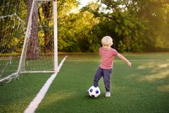 Little boy having fun playing a soccer/football game on summer day. Active outdoors game/sport for children. Kids soccer classes and camps royalty free stock images
