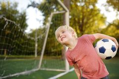 Little boy having fun playing a soccer/football game on summer day. Active outdoors game/sport for children. Kids soccer classes and camps stock photography