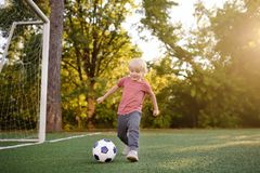 Little boy having fun playing a soccer/football game on summer day. Active outdoors game/sport for children. Kids soccer classes and camps stock image