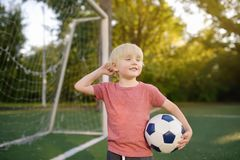 Little boy having fun playing a soccer/football game on summer day. Active outdoors game/sport for children. Kids soccer classes and camps stock photo