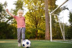 Little boy having fun playing a soccer/football game on summer day. Active outdoors game/sport for children stock photos