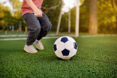Little boy having fun playing a soccer/football game on summer day. Active outdoors game/sport for children royalty free stock image