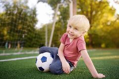 Little boy having fun playing a soccer/football game on summer day. Active outdoors game/sport for children royalty free stock photo