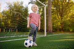 Little boy having fun playing a soccer/football game on summer day. Active outdoors game/sport for children royalty free stock photos
