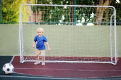 Little boy having fun playing a soccer/football game on summer day Stock Photo