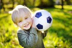 Little boy having fun playing a soccer game on sunny summer day stock photos