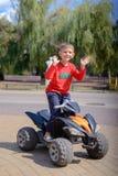 Little boy having fun on a quad bike Stock Images