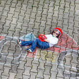 Little boy having fun with race car drawing with chalks Stock Images