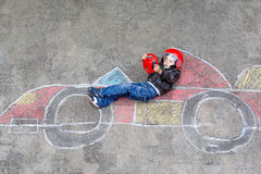 Little boy having fun with race car drawing with chalks. Funny kid boy having fun with race car picture drawing with colorful chalks. Creative leisure for Royalty Free Stock Photo