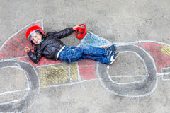 Little boy having fun with race car drawing with chalks Royalty Free Stock Images