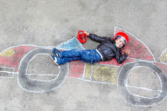 Little boy having fun with race car drawing with Royalty Free Stock Image