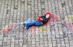 Little boy having fun with race car picture drawing with chalk Stock Images