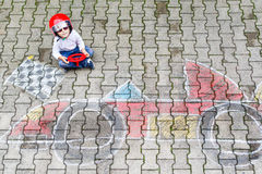 Little boy having fun with race car picture drawing with chalk Royalty Free Stock Photography
